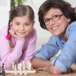 Woman playing chess with little girl — Stock Photo