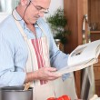 Senior citizen cooking with recipe book — Stock Photo