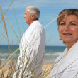 Stock Photo: Mature couple wearing bathrobe at beach.