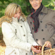 Couple collecting chestnuts in basket — Stock Photo #7745297