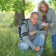 Couple inspecting plants in the forest and making a log — Stock Photo