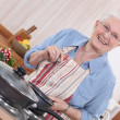 Old lady cooking in kitchen — Stock Photo