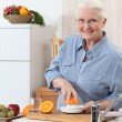 Stock Photo: Old lady pressing oranges.