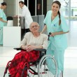 Nurse pushing an older woman in a wheelchair — Stock Photo