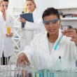 Female trio in lab with test-tubes — Stock Photo