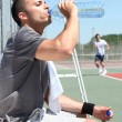Man drinking water on tennis court sideline - Foto Stock