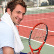 Young tennis player sitting on the court sidelines - Stock Photo