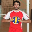 Stock Photo: Volleyball player with ball in front of net