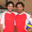 Stock Photo: Team mates stood with volley ball on indoor court