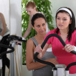 Female riding a bike in the gym — Stock Photo #7749261
