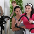 Female riding a bike in the gym — Stock Photo