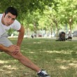 Young man doing stretching exercises in park — Stock Photo #7749720