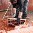 Workman sculpting a brick - Foto Stock