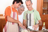 A 20 years old boy and 65 years old man and woman making cake together — Stock Photo