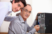 Father and son fixing a computer — Stock Photo