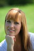 Kobieta siedzi na trawie, kontemplując aparatu — Zdjęcie stockowe