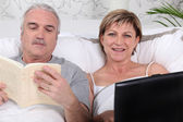 Mature couple relaxing in bed — Stock Photo