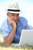 年配の男性人は草の上に横たわって彼のラップトップを使用して — ストック写真