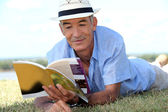 Elderly gentleman lying on grass reading tourist guide — Stock Photo