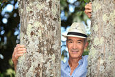 Old man stood between two trees — Stock Photo