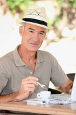 Older man outside with a laptop and an expresso — Stock Photo