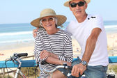 Senior couple riding bikes by the ocean — Stock Photo