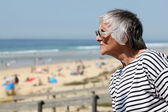 Senior woman looking out over a sandy beach on a summer day — Stok fotoğraf