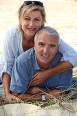 Couple sitting on a sand dune — Stock Photo