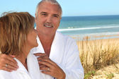 Reife frau blickte liebevoll bei ihren partner in den sanddünen — Stockfoto