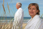 A mature couple wearing bathrobe at the beach. — Stock Photo