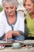 Two women looking through family photo album — Stock Photo