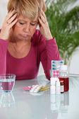 Senior woman taking pills — Stock Photo