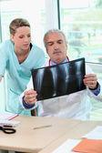 Médecin et infirmière examinant un radiographie du thorax  — Photo