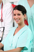 Beaming brunette nurse sitting at desk with standing colleagues in backgrou — Stock Photo