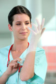 Female doctor putting on rubber gloves — Stock Photo