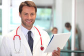 Hospital doctor checking patient notes — Stock Photo