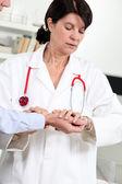 Woman taking a patient's blood pressure — Stock fotografie