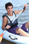 Young man paddling a kayak — Stock Photo