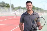 Tenista posando na frente de um campo de ténis — Foto Stock
