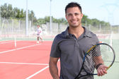 Tennis player posing in front of a tennis court — ストック写真