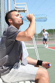 Man drinking water on tennis court sideline — Stock Photo