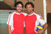 Team mates stood with volley ball on indoor court — Stock Photo