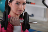 A woman raising a dumbbell — Stock Photo