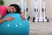Sportiva donna appoggiata su un pallone fitness — Foto Stock