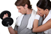 Young sporty man lifting weight encouraged by girlfriend — Stock Photo