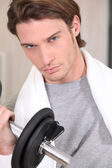 Portrait of a determined man lifting a dumbbell — Stock Photo