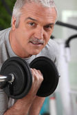 Man lifting a dumbbell at the gym — Stock Photo
