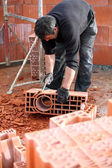 Workman sculpting a brick — Stock Photo