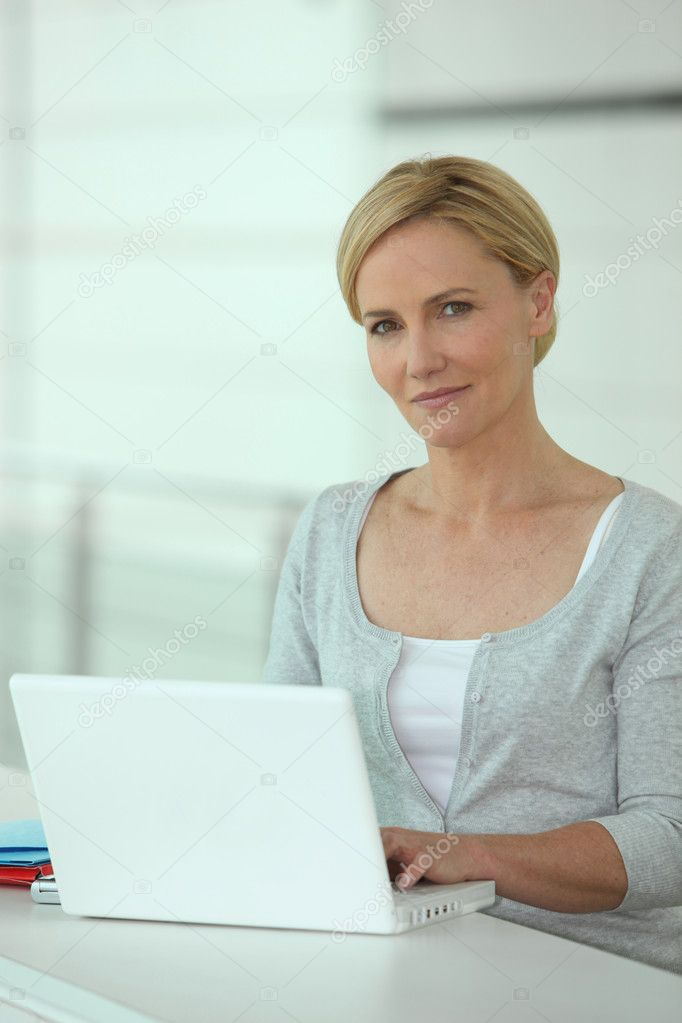 Woman working at a white laptop computer  Stock Photo #7743247