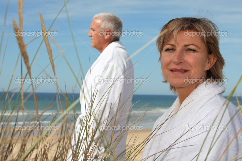 A mature couple wearing bathrobe at the beach. — Stock Photo #7745045